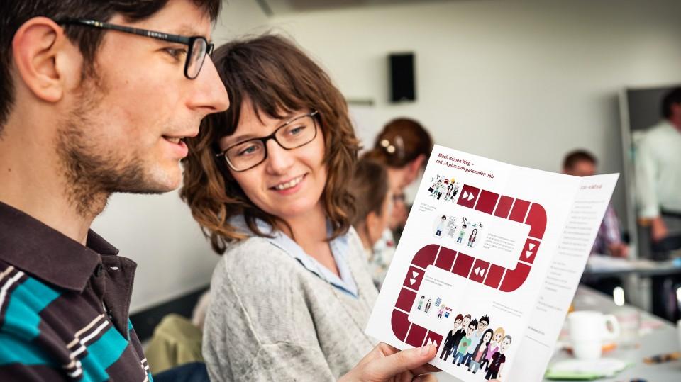 Foto: Mann und Frau schauen sich einen Flyer an