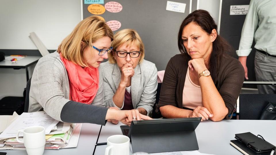 Foto: Drei Frauen schauen sich am Tablet was an