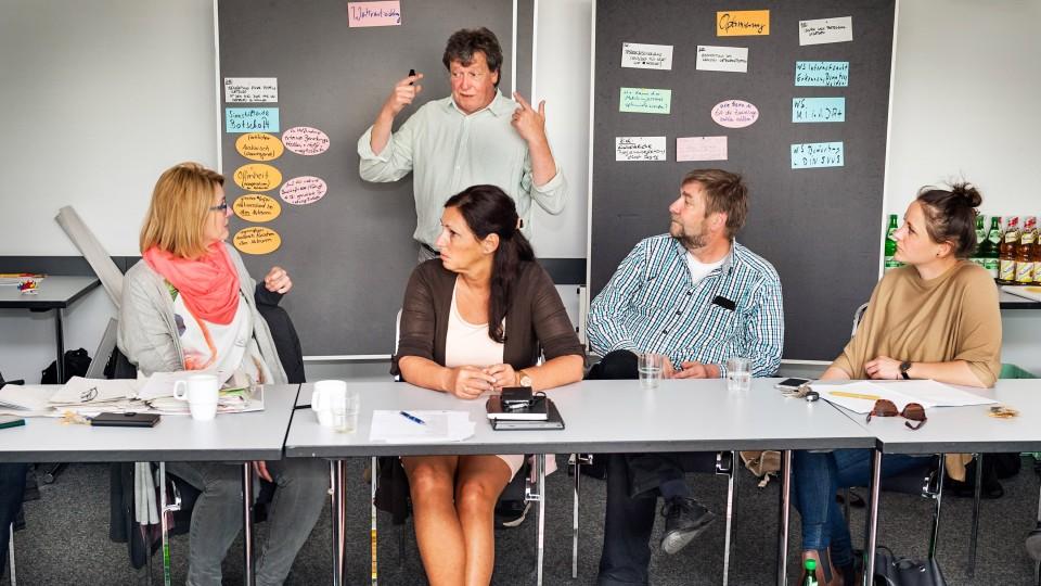 Foto: Zwei Männer und drei Frauen bei einer Diskussionsrunde