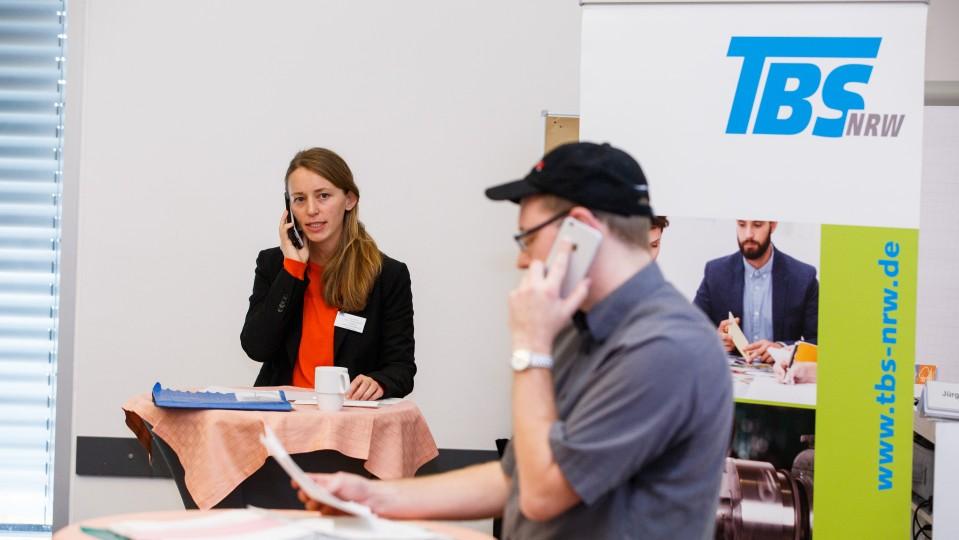 Eine Frau und ein Mann mit Telefonhörer am Ohr - TBS-Roll-up im Hintergrund