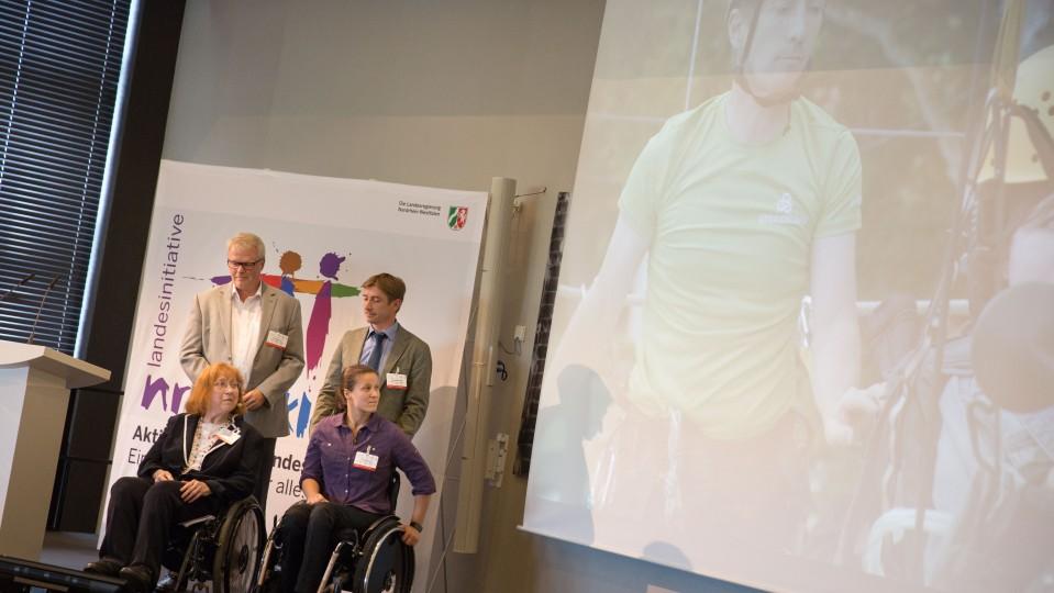 Zwei Preisträgerinnen im Rollstuhl und 2 Männer vor Plakat Inklusionspreis NRW
