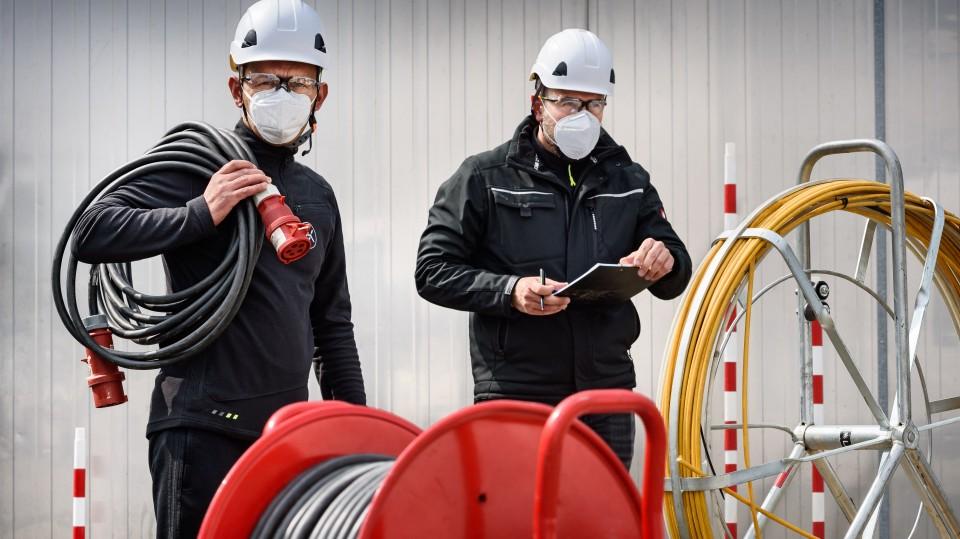 Zwei Kabelverleger mit Mundschutz, im Vordergrund Kabelrolle