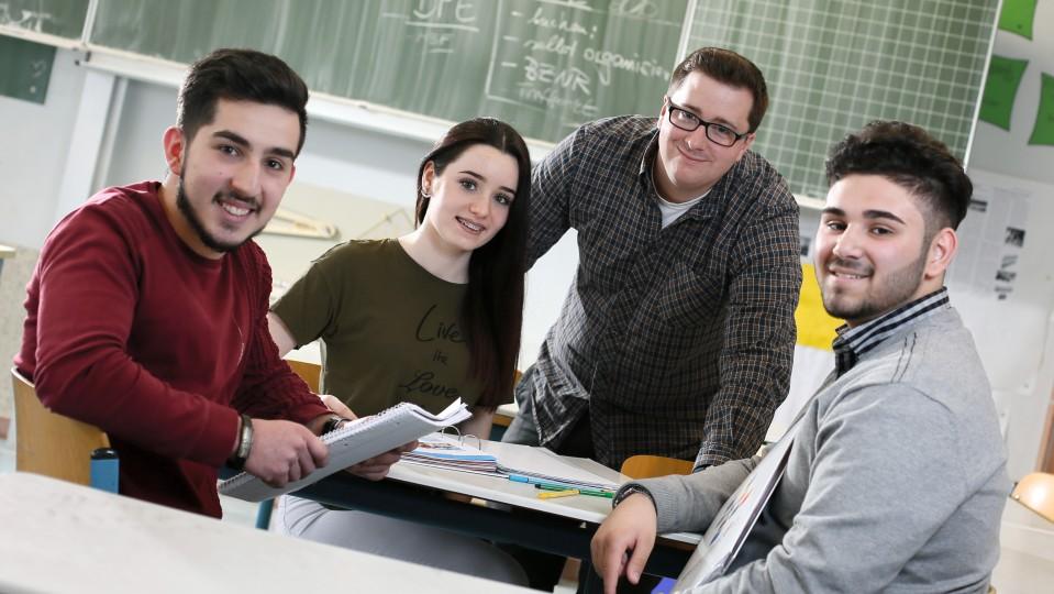 SchülerInnen mit Lehrer vor Schultafel