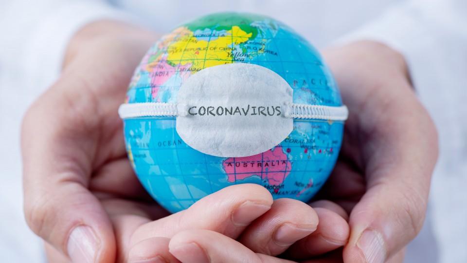Foto zeigt Globus mit Schutzmaske gegen Coronavirus in den Händen eines Mannes mit DoktorkittelDoktors