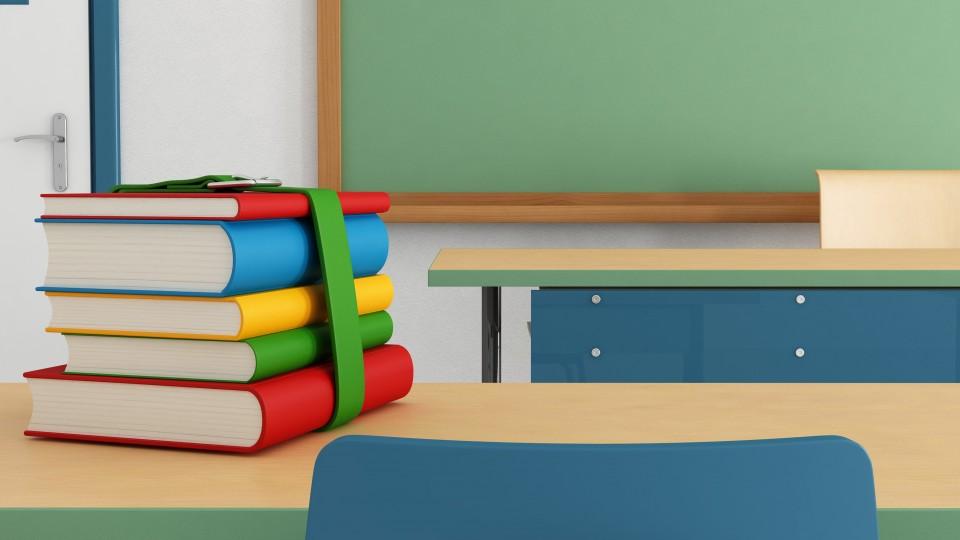Foto zeigt Schulbücher auf einem Tisch vor einer Tafel im Klassenzimmer