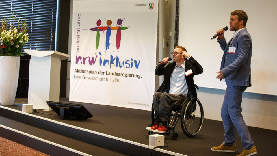 Foto: Zwei Männer rappen. Einer davon sitzt im Rollstuhl