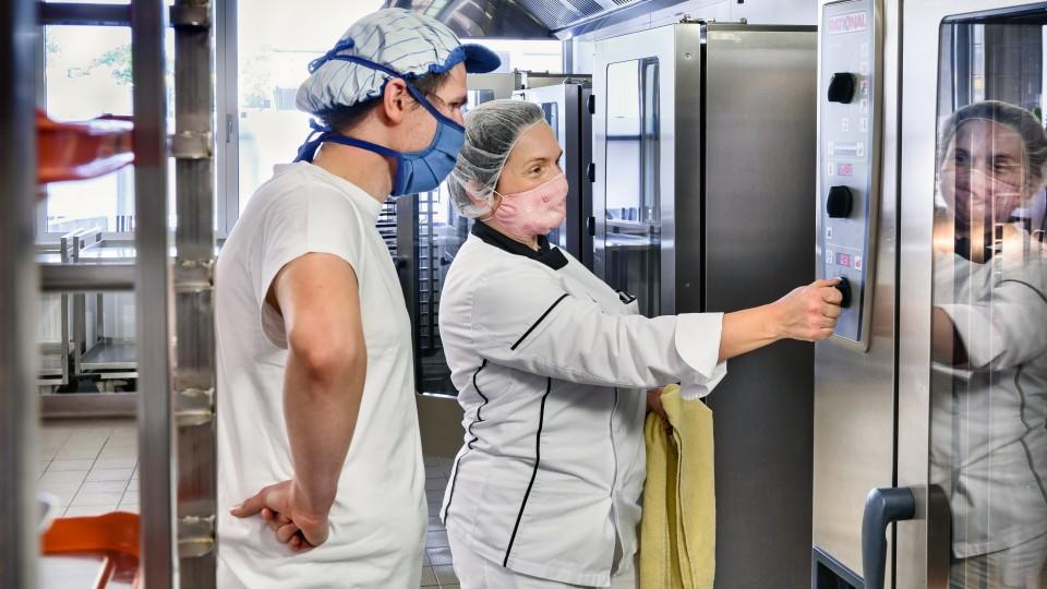 ÖgB-Teilnehmer und Anleiterin, mit Mundschutz in Größküche