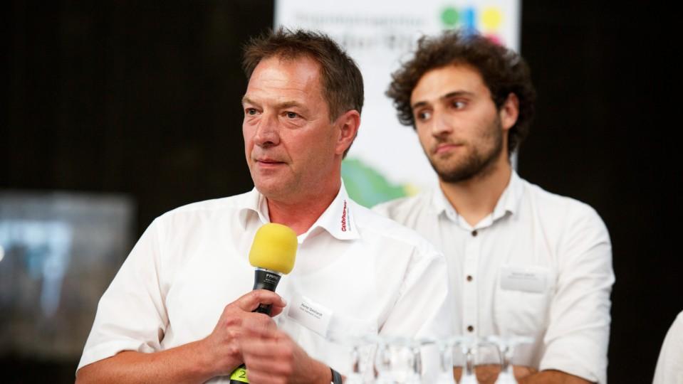 Foto: Dirk Gebhardt, Geschäftsführer der Horst Gebhard Malerbetrieb GmbH, hält das Mikrofon