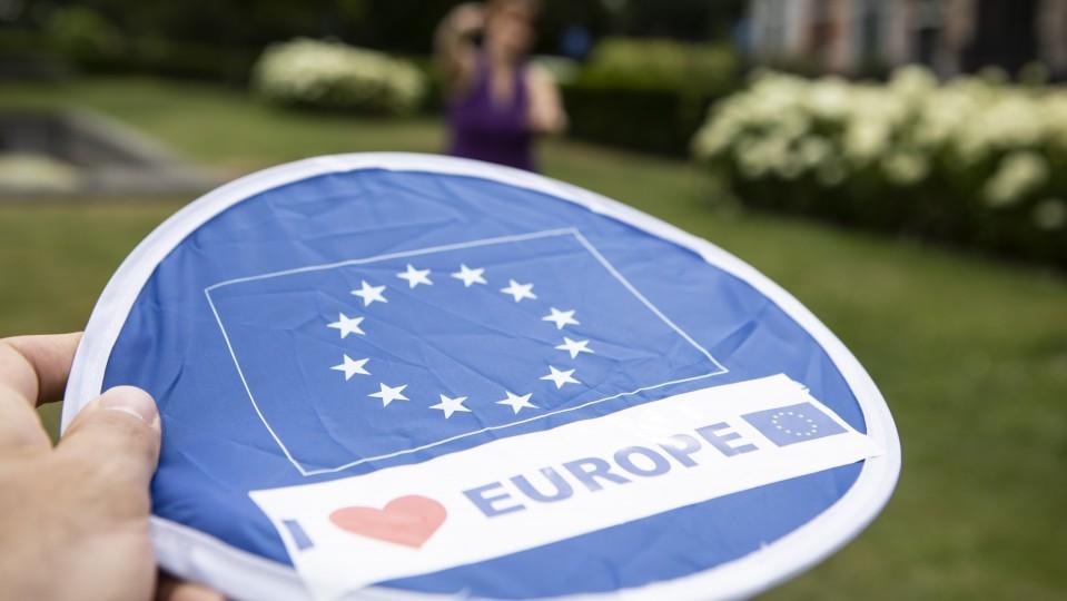 Hand hält Frisbee-Scheibe mit EU-Symbol, im Hintergrund Mitspielerin