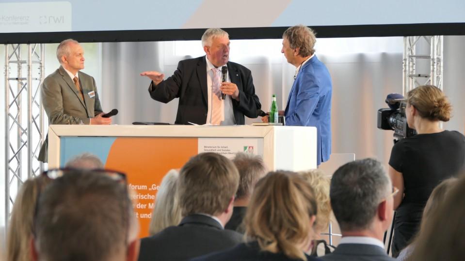 Gesundheitsminister Karl-Josef Laumann und Prof. Dr. Christoph M. Schmidt mit Moderator auf der Bühne der Ruhr-Konferenz