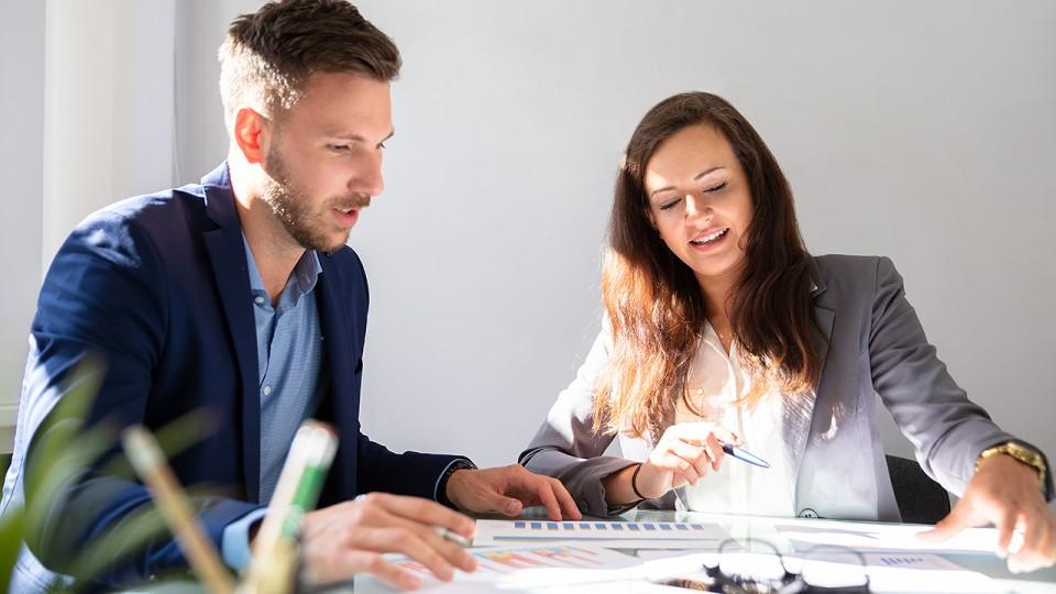Zwei junge Geschäftsleute analysieren eine Grafik