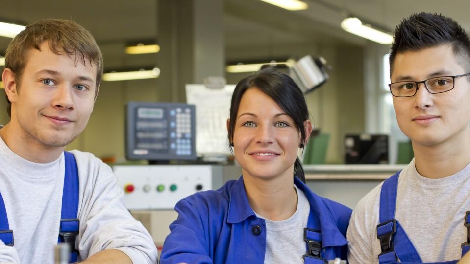 Drei Auszubildende in blauer Arbeitskleidung in Werkhalle