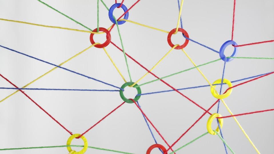 Bunte Bänder schaffen Verbindungen zwischen vielfarbigen Ringen und schaffen so ein Netzwerk.