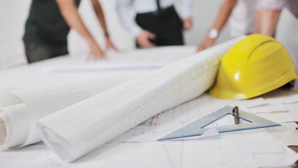 Tisch auf dem mehrere Papierrollen, ein Bauhelm und ein Linealdreieck liegen.