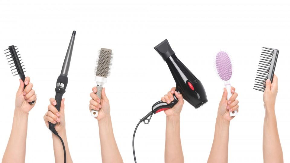 Foto zeigt Hände, die Ausstattung für Friseure halten
