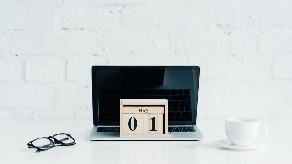 Laptop mit einer Brille und einer Tasse Kaffee auf einem Tisch. Auf dem Laptop steht ein Holzkalender, der auf den 1. Mai eingestellt ist.