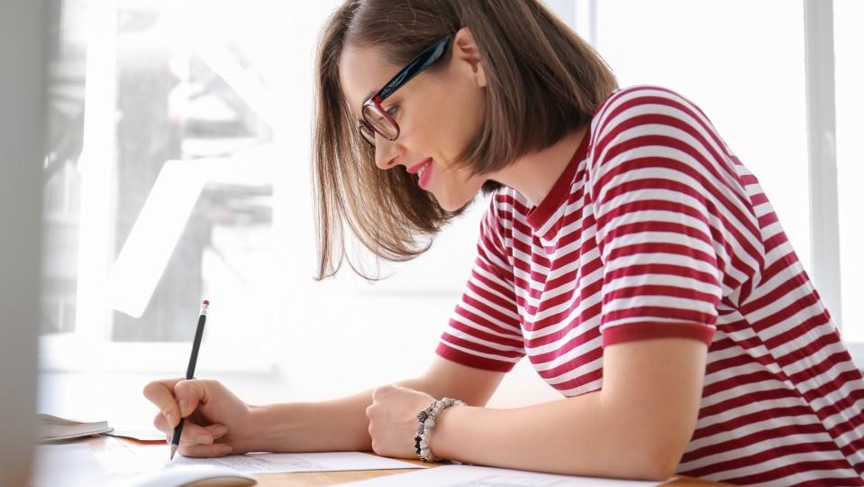 Eine Frau sitzt an einem Schreibtisch und schreibt