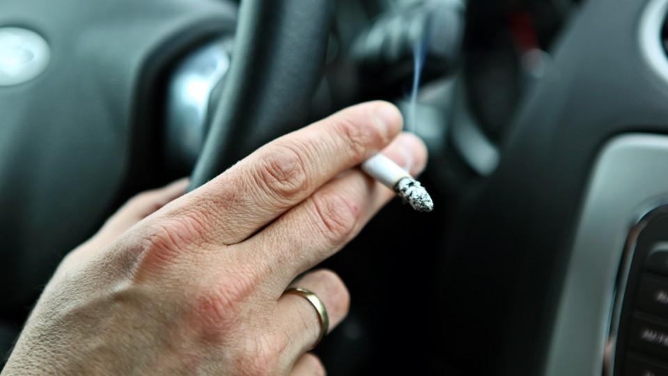 Bild zeigt die Rechte Hand eines Mannes am Steuer eines Autos. Die Hand hält eine Zigarrette.