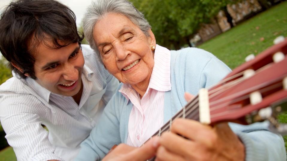 Ein jüngerer Gitarrenlehrer zeigt einer lebensalten Dame einen Gitarrengriff - beide lächeln.