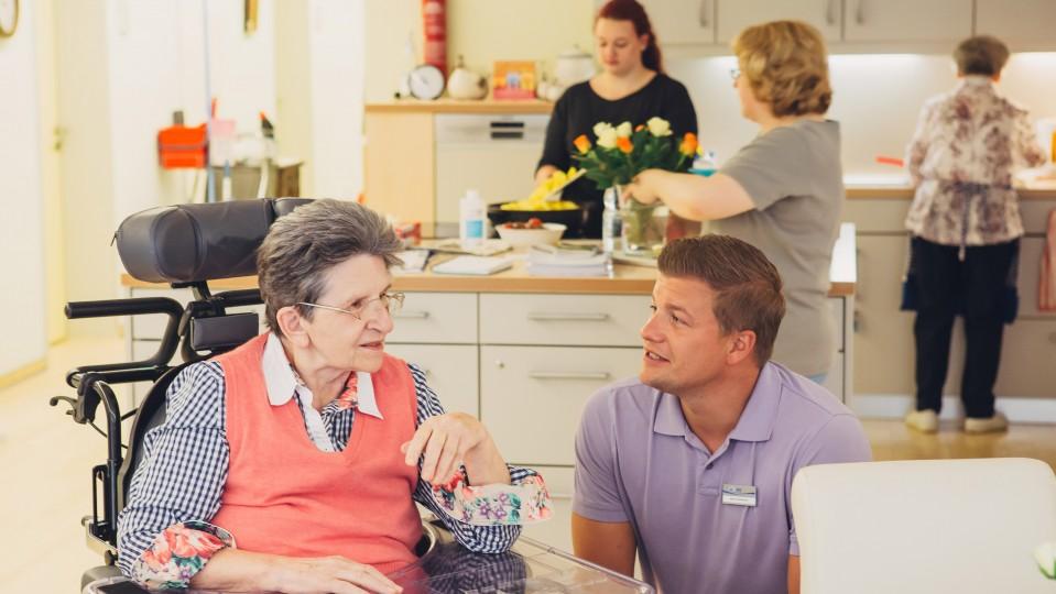 Foto zeigt ältere Dame mit Pfleger im Pflegeheim