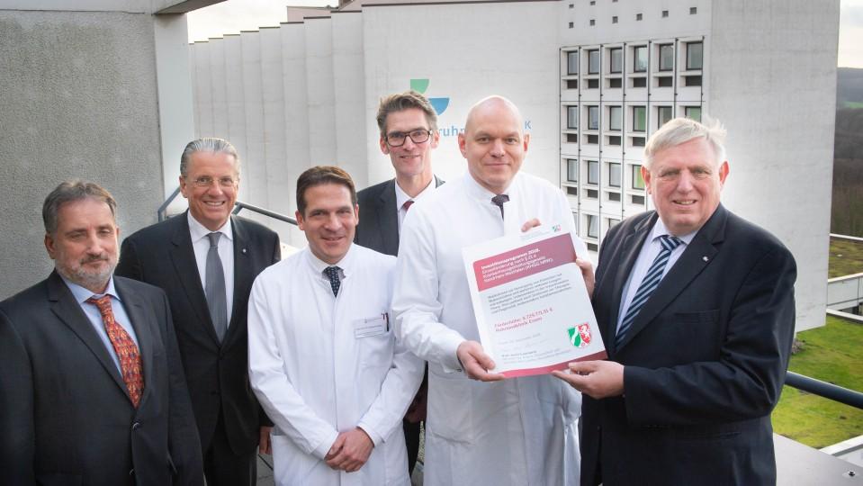 Minister Laumann übergibt einen symbolischen Förderbescheid an  den Geschäftsführer der Ruhrlandklinik und Kaufmännischer Vorstand des Universitätsklinikum Essen, Thorsten Kaatze, und weiteren Beschäftigten der Klinik.