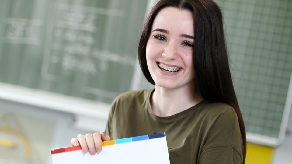 Schülerin zeigt Lernmaterial, im Hintergrund Schultafel