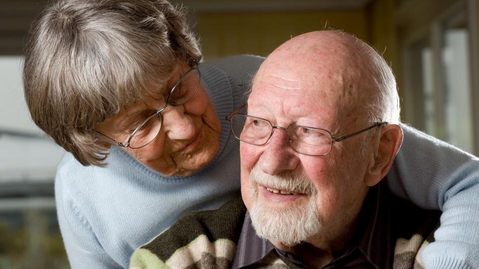 Foto zeigt eine ältere Frau mit einem Arm auf der Schulter eines älteren Mannes