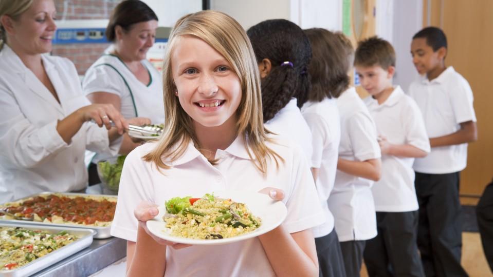 Lächendes Mädchen hält ihr Mittagessenteller in die Kamera. Im Hintergrund sind Kinder in der Schlange zur Essensausgabe.