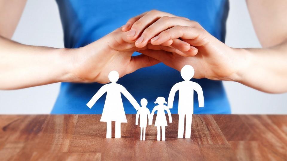 Eine Frau hält ihre Hände über eine Scherenschnittfamilie