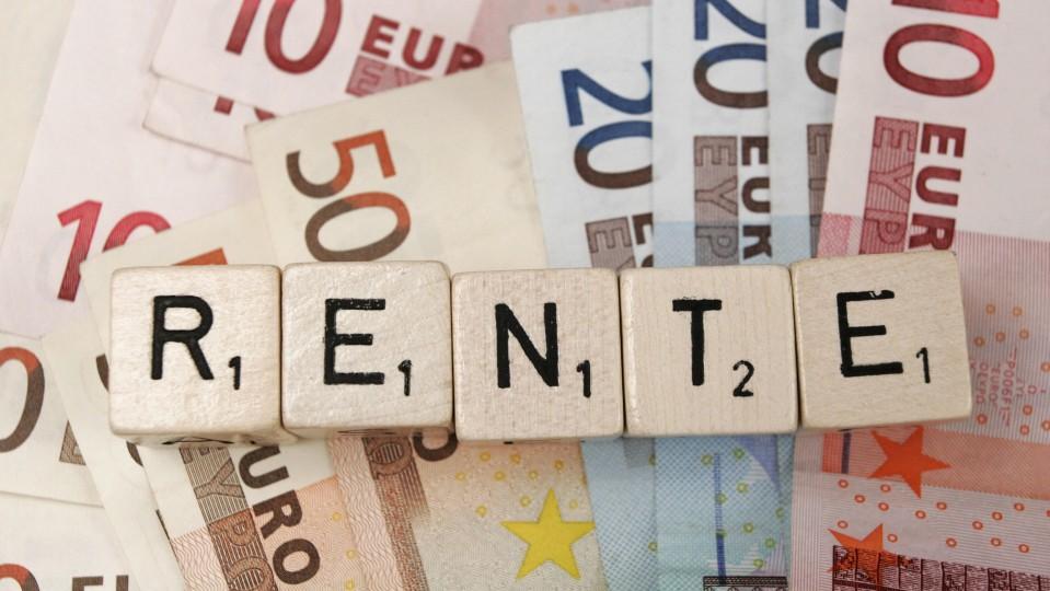 Fotos zeigt Spieltsteine die das Wort Rente bilden vor Euroscheinen