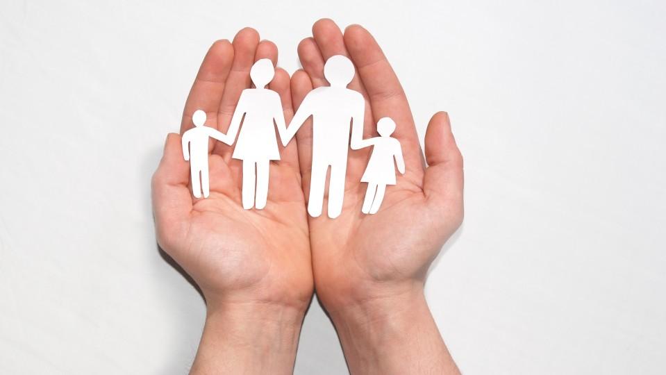 Eine Scherenschnittfamilie liegt in Händen