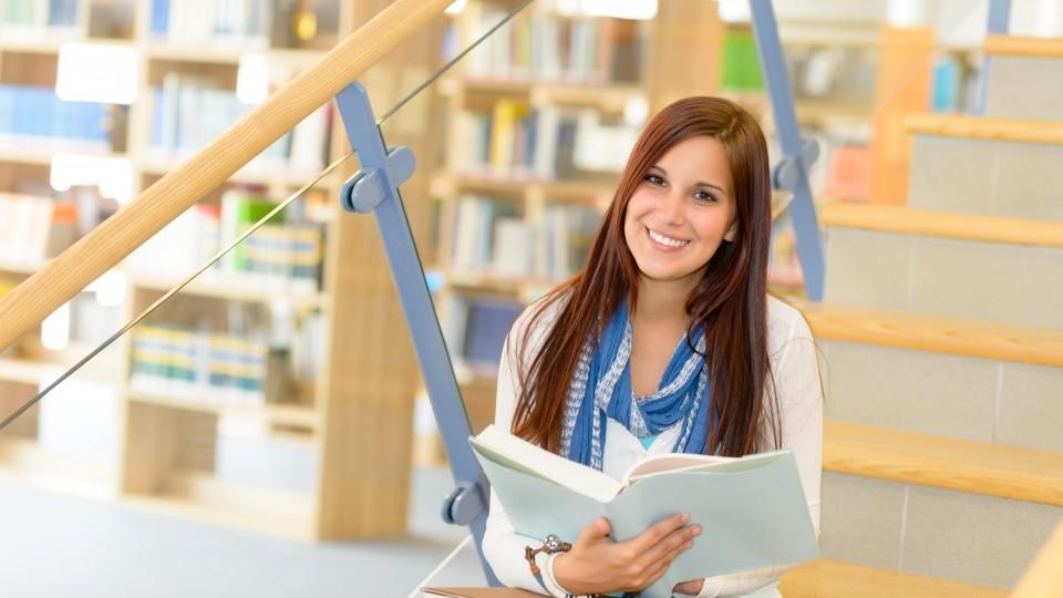 Junge Frau, die in einem Buch blättert und auf einer Treppe sitzt