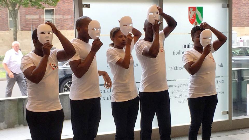 """Fünf Mitglieder der Pantomime-Gruppe """"Mime Art for Life"""" stehen nebeneinander und setzen weiße Masken auf."""