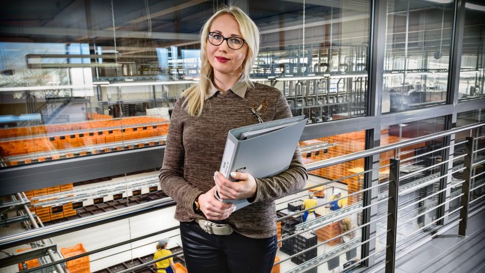 Junge Frau mit Aktenordner im Arm steht an Geländer mit Blick auf Werkshalle