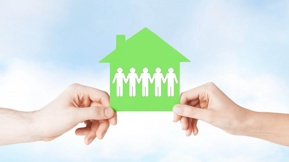 Zwei Hände halten ein aus Pappe ausgeschnittenes Haus. Auf ihm halten sich Scherenschnittfiguren an den Händen.