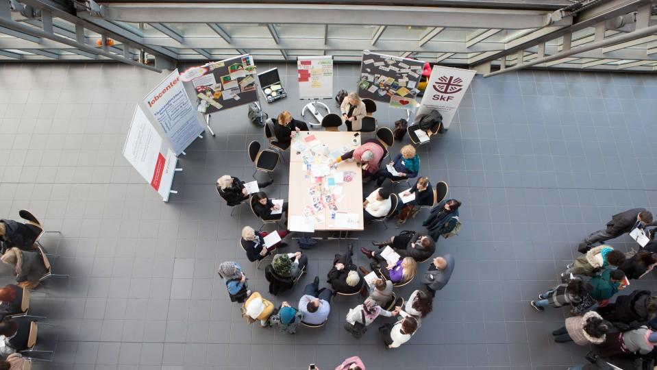 Blick von oben auf Konferenzteilnehmende, die am Thementisch diskutieren
