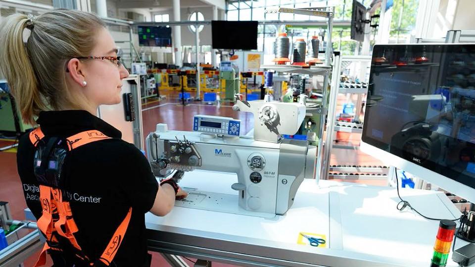 Eine Mitarbeiterin des Digital Capability Centers (DCC) arbeitet in Aachen am Montag 19. Juni 2017 an einer digitalen Etiketten-Webmaschine. Auf ihrem Rücken ist ein ein Assistenzsystem um die Arbeitsvorgänge aufzuzeichnen und zu verbessern.
